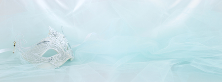 Banner of elegant and delicate white lace venetian mask over mint chiffon background Stock Photo