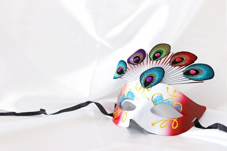Photo of elegant and delicate venetian mask with peacock tail decoration element over white silk background