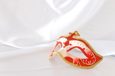 Photo of elegant and delicate red and gold venetian mask over white silk background
