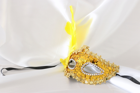 Photo of elegant and delicate gold venetian mask over white silk background Stock Photo