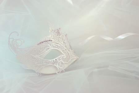 Photo of elegant and delicate white lace venetian mask over mint chiffon background