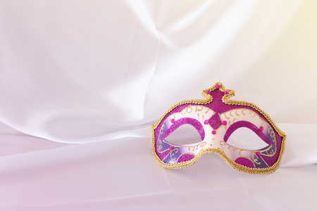 Photo of elegant and delicate pink, purple and gold venetian mask over white silk background