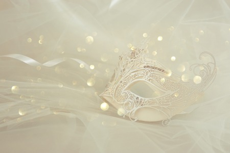 Photo of elegant and delicate white lace venetian mask over chiffon background