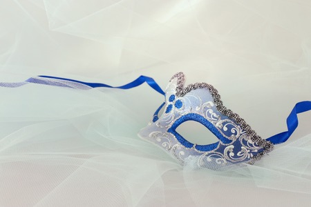 Photo of elegant and delicate silver and blue venetian mask over chiffon background