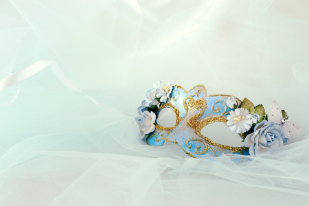 Photo of elegant and delicate blue venetian mask with floral decorations over mint chiffon background