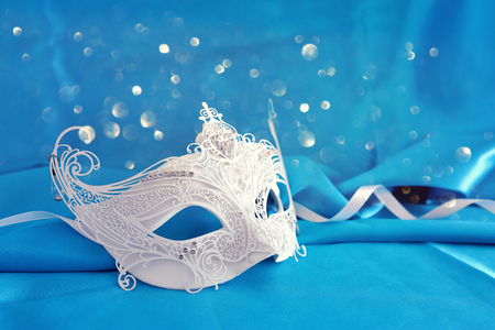 Photo of elegant and delicate white lace venetian mask over light turquoise silk background Stock Photo