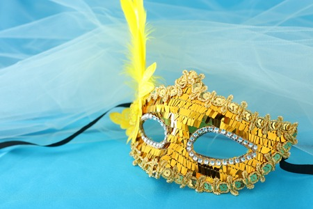 Photo of elegant and delicate gold venetian mask over turquoise silk and chiffon background