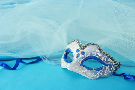 Photo of elegant and delicate silver and blue venetian mask over turquoise silk and chiffon background