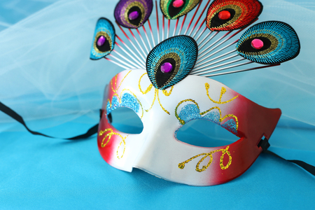 Photo of elegant and delicate venetian mask with peacock tail decoration element over turquoise silk background