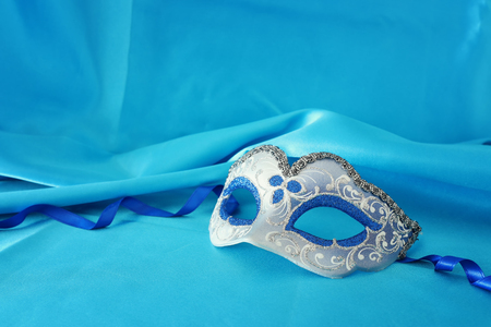 Photo of elegant and delicate silver and blue venetian mask over turquoise silk background