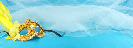 Banner of elegant and delicate gold venetian mask over turquoise silk and chiffon background
