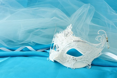 Photo of elegant and delicate white lace venetian mask over light turquoise silk and chiffon background
