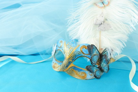 Photo of elegant and delicate gold and blue venetian mask over turquoise silk and chiffon background