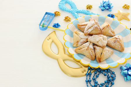 Purim celebration concept (Jewish carnival holiday) over white wooden background. Top view, Flat lay