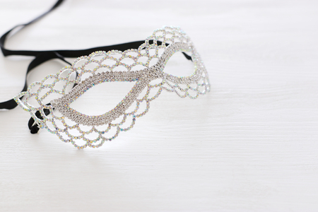 Photo of elegant and delicate silver diamond Venetian mask over white wooden background Stock Photo