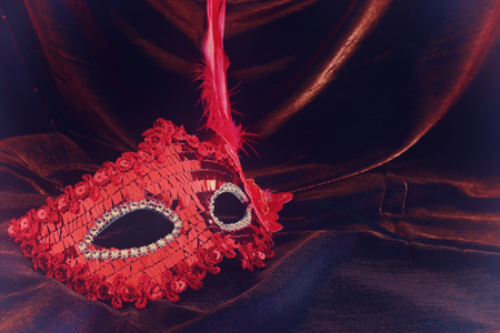 Photo of elegant and delicate red Venetian mask over dark velvet and silk background Stock Photo