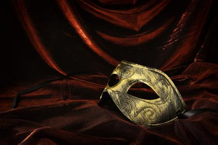Photo of elegant and delicate gold Venetian mask over dark velvet and silk background Stock Photo