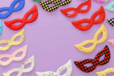 carnival party celebration concept with collection of colorful masks over purple wooden background. Top view. Flat lay.