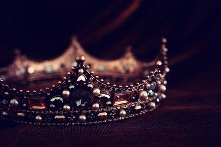 photo of gold crown over gothic dark silk background. Medieval period concept