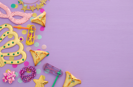 Purim celebration concept (jewish carnival holiday) over wooden pink background.