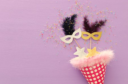 carnival party celebration concept with mask over purple wooden background. Top view. Flat lay