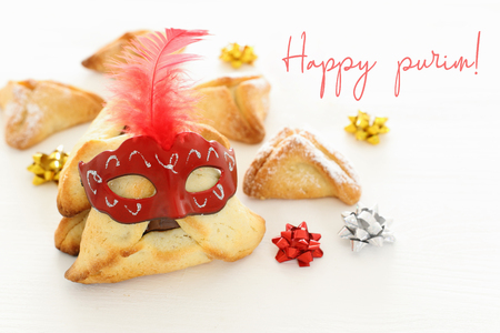 Purim celebration concept (jewish carnival holiday). Traditional hamantaschen cookies with cute mask over white wooden table