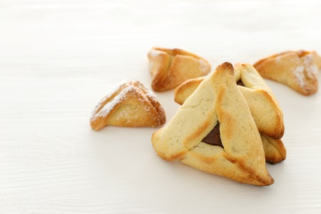 Purim celebration concept (jewish carnival holiday). Traditional hamantaschen cookies over white wooden table 版權商用圖片