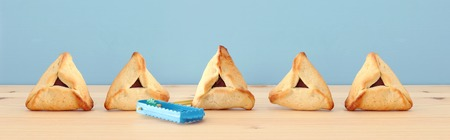 Purim celebration concept (jewish carnival holiday). Traditional hamantaschen cookies over wooden table and blue background Imagens