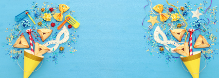 Purim celebration concept (jewish carnival holiday) over wooden blue background. Banner