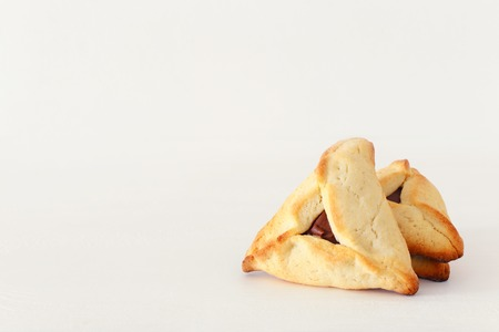Purim celebration concept (jewish carnival holiday). Traditional hamantaschen cookies over white wooden table Stock Photo