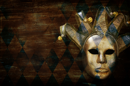 Silver with gold elegant traditional Venetian mask over dark wooden background Stock Photo
