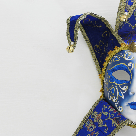 Blue with gold elegant traditional Venetian mask over white wooden background