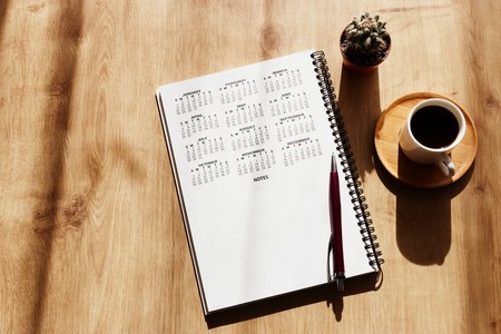 Coffee cup and calendar over wooden table Stock fotó