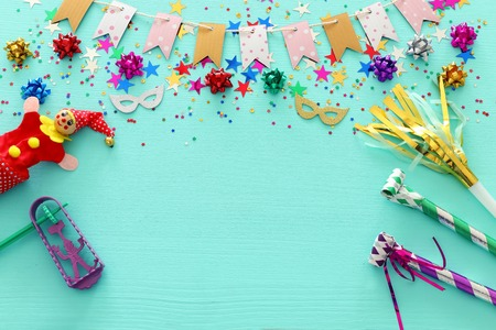 Party colorful confetti with noisemaker over light pastel blue wooden background . Top view, flat lay