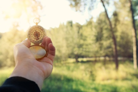 Male's hand holding a compass during travel in the forest