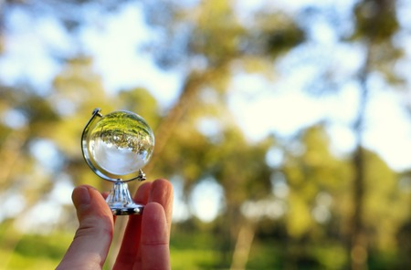 Small crystal globe in front of sunset. Travel and global issues concept