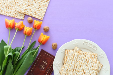 Pesah celebration concept (jewish Passover holiday). Traditional book with text in hebrew: Passover Haggadah (Passover Tale) and plate with word PASSOVER Stock Photo