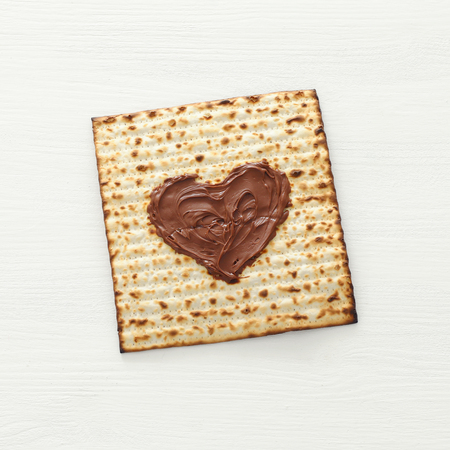 Pesah celebration concept (jewish Passover holiday) with chocolate heart over matzah. Top view flat lay