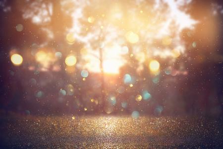 blurred abstract photo of light burst among trees and glitter golden bokeh lights Stock fotó