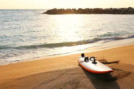Surfboard on sandy beach during sunset time