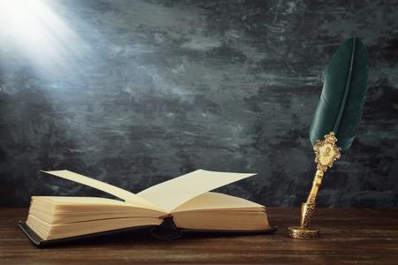 Vecchia penna a inchiostro con penna d'oca con calamaio e vecchi libri sulla scrivania in legno davanti allo sfondo nero della parete. Vintage vecchio stile e filtrato. Foto concettuale su argomenti di storia, fantasia, educazione e letteratura