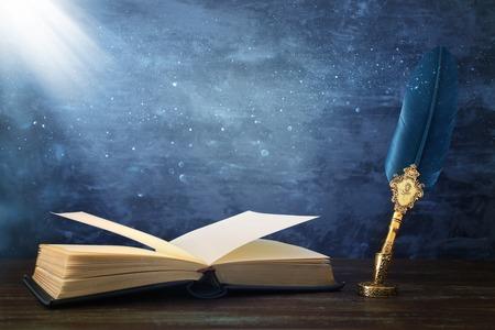 Pluma vieja de la tinta de la canilla de la pluma con el tintero y los libros antiguos sobre el escritorio de madera delante de la pared negra del fondo. Estilo antiguo vintage y filtrado. Fotografía conceptual sobre el tema de la historia, la fantasía, la educación y la literatura Foto de archivo