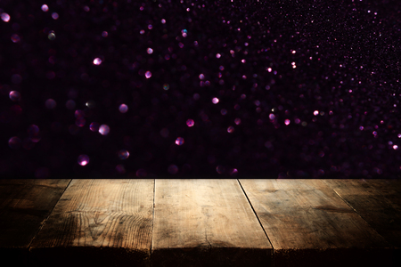 Wooden table in front of glitter black and gold bokeh lights. For product presentation