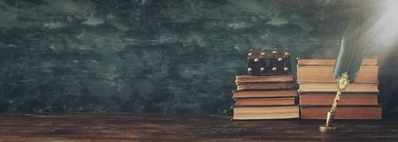 Alter Federkieltintenstift mit Tintenfass und alten Büchern über Holzschreibtisch vor schwarzem Wandhintergrund. Vintage im alten Stil und gefiltert. Konzeptfoto zum Thema Geschichte, Fantasie, Bildung und Literatur and Standard-Bild