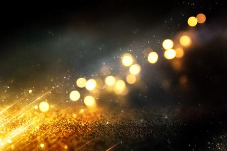 Tło wzór światła świecidełka. Czarny i złoty. Nieostre.