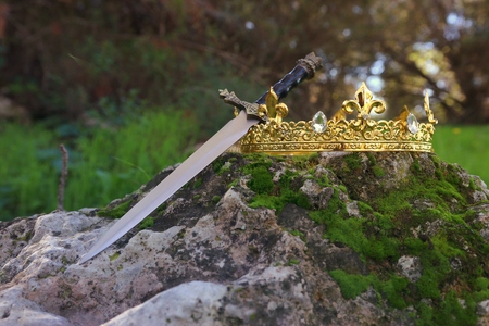 mysterious and magical photo of gold king crown and sword in the England woods over stone covered with moss. Medieval period concept.
