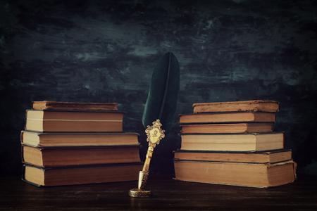 Ancien stylo à encre plume avec encrier et vieux livres sur un bureau en bois devant un fond de mur noir. Photo conceptuelle sur le sujet de l'histoire, de la fantaisie, de l'éducation et de la littérature.