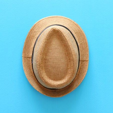 Top view of male fedora hat over blue background