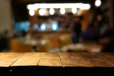 Image of wooden table in front of abstract blurred restaurant lights background 免版税图像