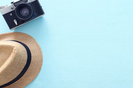 Top view photo of traveling concept with fedora hat and photo camera over blue background